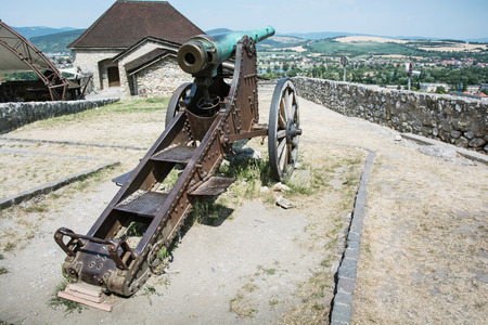 gunfire: Rusty historic cannon in Trencin castle, Slovak republic. Museum of history. Vintage heavy weapon. Military theme.
