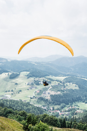 leisure activities: Paragliding, Donovaly, mountains scene, Slovak republic. Leisure activities. Vertical composition. Beauty in nature. Adrenaline sport. Stock Photo