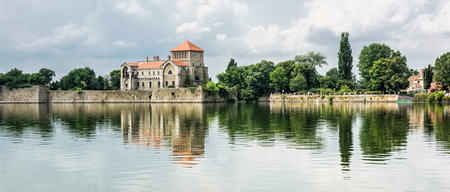 Beautiful castle with greenery and cloudy sky in Tata, Hungary. Travel destination. Architectural theme. Beautiful place. Fortress is reflected in the lake. Redakční