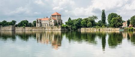 Krásný zámek se zelení a zamračená obloha v Tatu, Maďarsko. Cíl cesty. Architektonické téma. Krásné místo. Pevnost se odráží v jezeře.