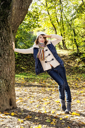 beech tree beech: Beautiful young positive woman saluting under the beech tree in autumn nature. Seasonal fashion. Vibrant colors. Vertical composition.