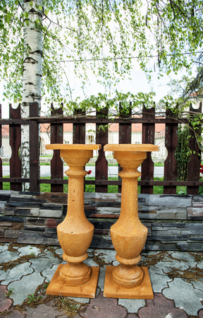 the stands: Two terracotta flower stands at the garden. Gardening theme. Decorative objects. Vertical composition.