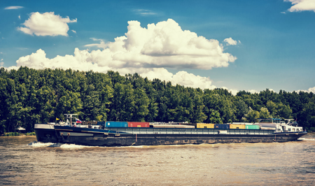 Cargo ship with containers on the Danube river, Slovak republic. Goods transport. Blue retro photo filter. Freight transportation. Against the flow. Clouds in the sky.