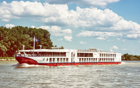 cruiseship: Cruise ship and Danube river. Travelling scene. Beautiful place. Travel destination. Clouds in the sky. Seasonal outdoors scene. Retro photo filter. Summer vacation. Tourism theme.
