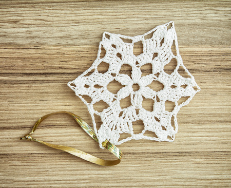 symbolic: White crochet christmas decoration on the wooden texture. Christian holiday. Symbolic object.