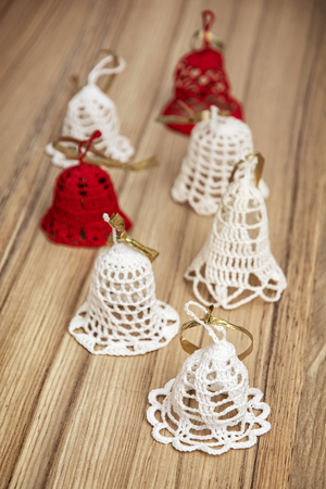 background texture metaphor: Beautiful red and white crochet christmas bells on the wooden texture. Merry Christmas. Vertical composition.