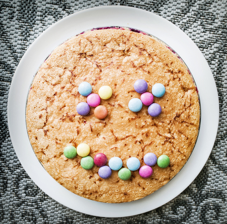 smarties: Tasty cake with colorful smarties in funny face shape. Festive sweet food. Positive emotions.