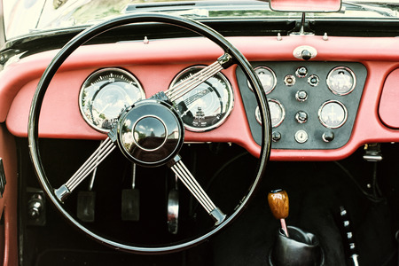 historic vintage: Steering wheel and dashboard in historic vintage red car. Retro automobile interior scene. Driving theme. Photo filter. Old vehicle.