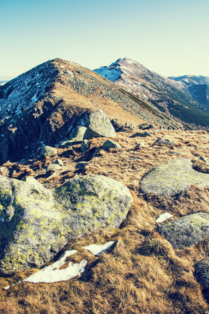 Footpath leading up the peak Dumbier, Low Tatras, Slovak republic. Hiking theme. Mountains scene. Retro photo filter. Stones, snow and dry grass.