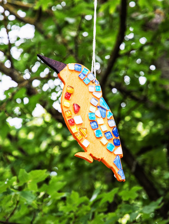 vertical composition: Beautiful ceramic decoration in the bird shape hanging on the green tree. Artistic object. Vertical composition. Vibrant colors.
