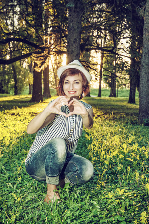 backlight: Young caucasian natural woman making heart shape in sunny backlight. Sexy female portrait. Big trees, green grass and long shadows. Retro photo filter. Stock Photo