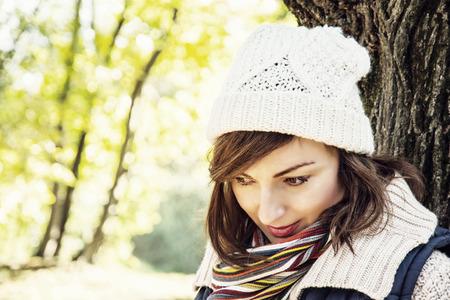 changing seasons: Young youful caucasian brunette woman posing in autumn park. Seasonal fashion. Female portrait. Vibrant colors.