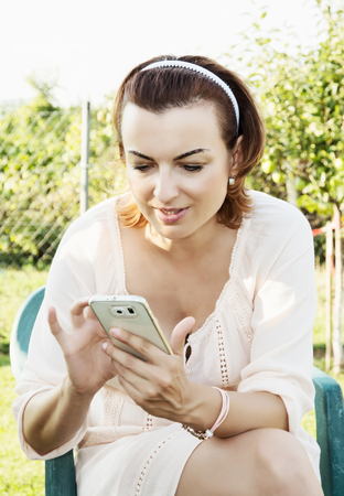 soltería: Young beautiful brunette woman writes on the white smartphone in outdoor. Female portrait. Positive emotions. Modern technology. Foto de archivo