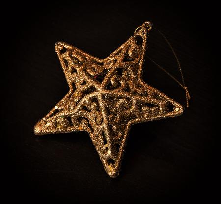 symbolic: Golden artistic christmas star on the dark background. Christian holiday. Symbolic object.