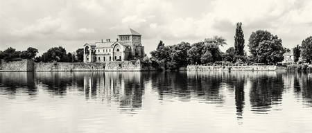 Beautiful castle with greenery and cloudy sky in Tata, Hungary. Travel destination. Architectural theme. Black and white photo. Fortress is reflected in the lake.
