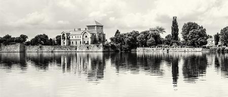Krásný zámek se zelení a zatažené obloze v Tata, Maďarsko. Cílové místo cesty. Architektonické téma. Černobílá fotografie. Pevnost se odráží v jezeře.