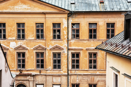 waterspout: Old abandoned house in Banska Stiavnica, Slovak republic. Architectural theme. Ancient building. Cracked wall. Impaired statics. Broken windows. Stock Photo