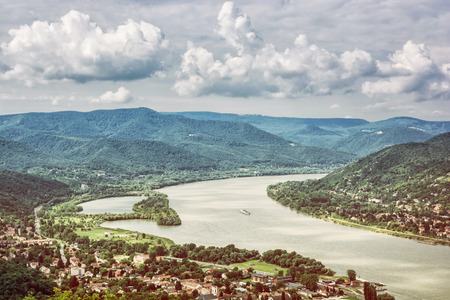 View from Ruin castle of Visegrad, Hungary. Danube river. Travel destination. Yellow photo filter. Sightseeing cruises. Forests, clouds and flowing water.