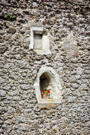 architectural  detail: Old window with potted red flowers. Architectural detail. Vertical composition.