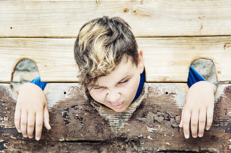 Young caucasian boy in medieval pillory. Negative emotions. Misery theme. Punishment device.