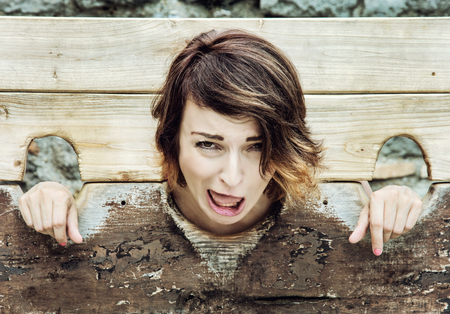 immobilize: Young caucasian brunette woman in medieval pillory. Negative emotions. Misery theme. Punishment device. Stock Photo