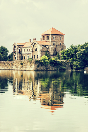 vertical composition: Beautiful castle in Tata, Hungary. Travel destination. Architectural theme. Beautiful place. Fortress is reflected in the lake. Retro photo filter. Vertical composition.