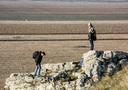 Young caucasian woman with teenage son on the Drazovce peak. Hiking theme. Autumn fashion. People, rocks and seasonal fields.