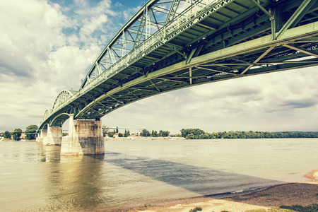 joins: Maria Valeria bridge joins Esztergom in Hungary and Sturovo in Slovak republic across the Danube river. Retro photo filter. Architectural scene. Transportation theme. Stock Photo
