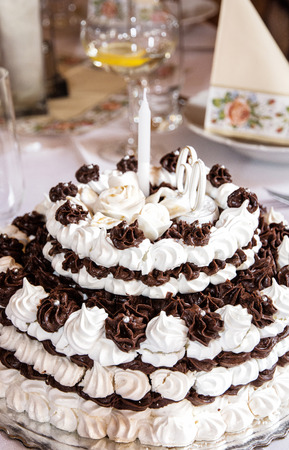 Big birthday chocolate and foam cake on the holiday table. Symbolic food. Vertical compostion. Food and drink.