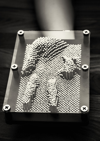 Victory sign on hand pressed to pin board toy forming. Leisure activity. Black and white photo.