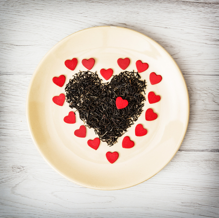 Heart of black loose tea from Ceylon and little red paper hearts on the plate. Valentines day. Symbol of lovers.