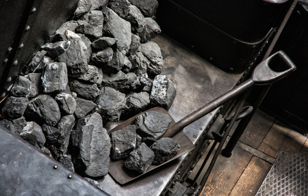 Shovel and coal in historic steam locomotive. Industrial revolution theme.