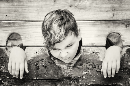 Young caucasian boy in medieval pillory. Negative emotions. Black and white photo. Punishment device.