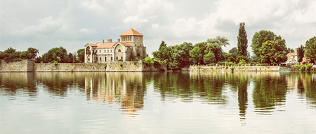 Beautiful castle with greenery and cloudy sky in Tata, Hungary. Architectural theme. Fortress is reflected in the lake. Photo filter. Reklamní fotografie