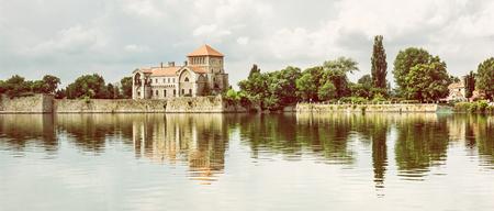 Krásný zámek se zelení a zamračená obloha v Tatu, Maďarsko. Architektonické téma. Pevnost se odráží v jezeře. Fotografický filtr.