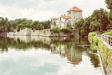 Krásný zámek v Tatu, Maďarsko. Cíl cesty. Architektonické téma. Pevnost se odráží v jezeře. Fotografický filtr.