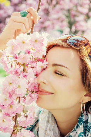 Young positive woman sniffs the branch of sakura. Glamour photo filter. Beauty and nature.
