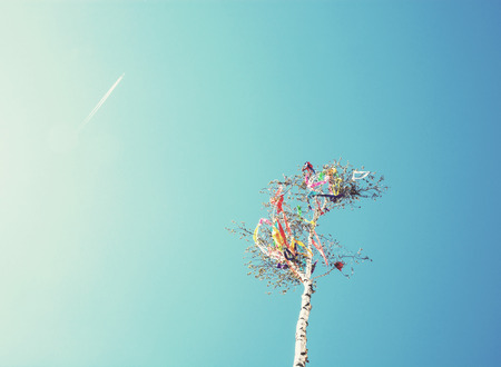 Looking up at may pole and aircraft on blue sky. European traditions. Photo filter.