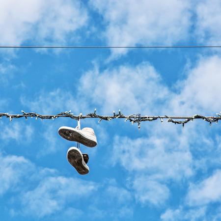Sneakers hanging on the power line. Blue sky. Bad joke.