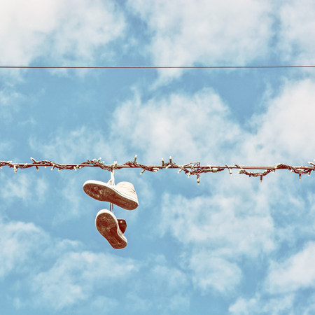 shoestrings: Sneakers hanging on the power line. Blue sky. Bad joke. Retro photo filter. Stock Photo