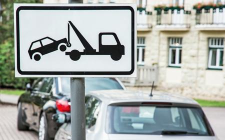 Señal de remolque. No hay lugar de estacionamiento. Los coches están estacionados en el estacionamiento de prohibición. Señal de tráfico. Foto de archivo - 82583591