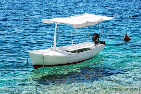 Anchored little boat in Maslinica, Solta island, Croatia. Summer vacation destination.