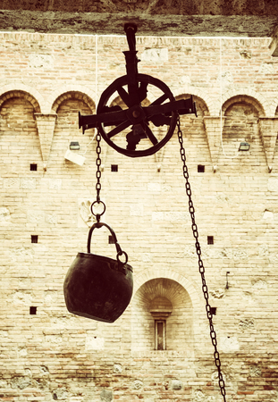 Metal bucket on a pulley hanging in the courtyard of the historic palace, Siena, Tuscany, Italy. Yellow photo filter. Stok Fotoğraf - 84447351