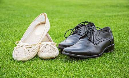 Womens and mens wedding shoes on the green grass. Symbol of love.