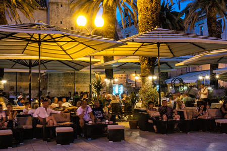 TROGIR, CROATIA – JULY 25, 2017: Many tourists are relaxing in an open-air bar at night, Trogir, Unesco, Croatia. Travel destination. Summer vacation. Illustrative editorial.