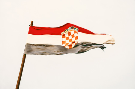 Croatian flag in the wind. Symbolic object. Yellow photo filter. Stock Photo