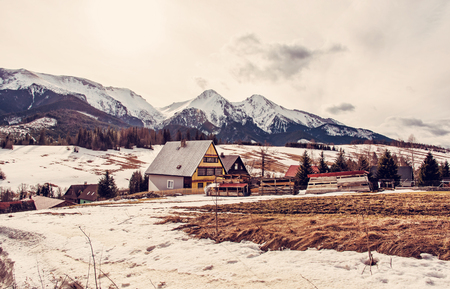 Folk architecture in Zdiar village with Belianske Tatry mountains, Slovak republic. Winter holiday resort. Travel destination. Red photo filter.