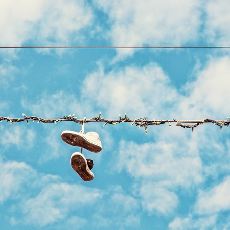 Sneakers hanging on the power line. Blue sky. Bad joke. Beauty photo filter.