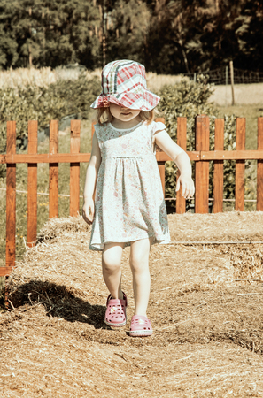Little girl is walking on the haystack. Leisure activity. Vintage filter. Stock Photo