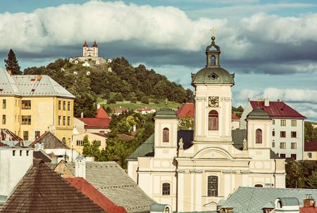 Calvary and Church of the assumption in Banska Stiavnica, Slovak republic. Sunset urban scene. Travel destination. Old photo filter. Stock Photo